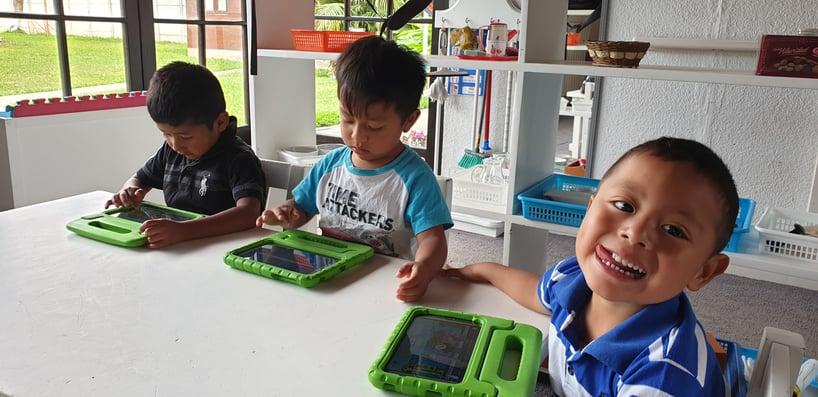 Guatemalan children using Moomin Language School on tablets