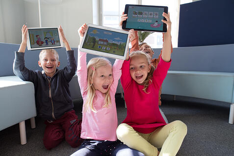 Three kids holding tablets and smiling