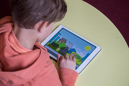 A young boy uses Moomin Language School on a tablet
