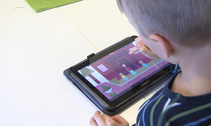 A child using Moomin Language School on a tablet
