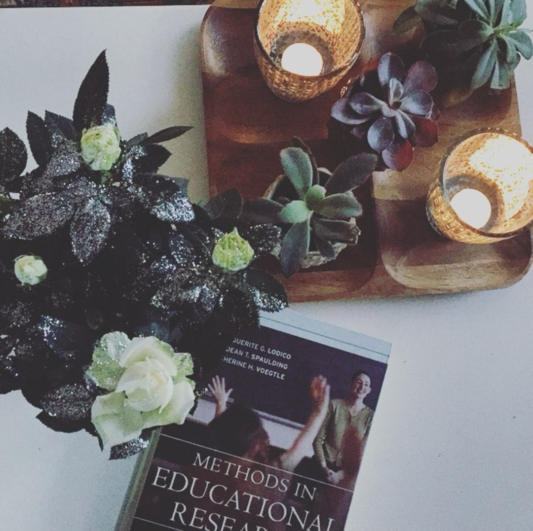 Methods in Educational Research book on a table with succulents and candles